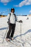 Het jonge mannetje in ski-kostuum, helm en skibeschermende brillen ski?t in sk stock fotografie