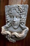 Het jonge masker van de vrouwensteen met decoratie van druiven stock foto