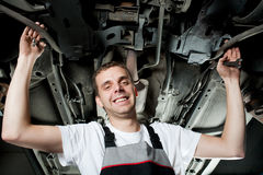 Het jonge mechanische werken onder de auto in garage Stock Afbeelding