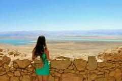 Het jonge meisje bekijkt het Dode Overzees Ruïnes van Herods-Kasteel in Masada-Vesting in Israël stock afbeelding