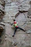 Het jonge meisje beklimt op een rots Royalty-vrije Stock Foto's