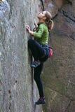 Het jonge meisje beklimt op een rots Stock Foto's