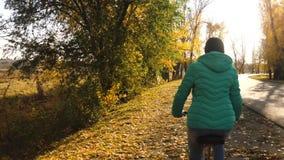Het jonge meisje berijdt fiets op kant van weg in de herfstpark op een achtergrond van gele bomen de rit van de sportenfiets stock video