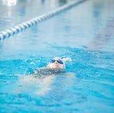Het jonge meisje in beschermende brillen die terug kruipt slagstijl zwemmen Stock Foto