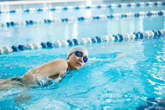 Het jonge meisje in beschermende brillen die voorzijde zwemmen kruipt slagstijl Stock Afbeelding