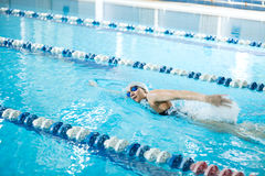 Het jonge meisje in beschermende brillen die voorzijde zwemmen kruipt slagstijl Stock Foto's