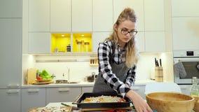 Het jonge meisje bestrooit een pizza met geraspte kaas stock videobeelden