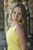 Het jonge meisje bevindt zich dichtbij een steenmuur Royalty-vrije Stock Foto