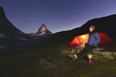 Het jonge meisje bevindt zich dichtbij haar tent met Matterhorn 4478m piek op achtergrond Stock Foto