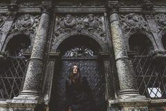 Het jonge meisje bevindt zich op de achtergrond van de oude gotische muur Stock Afbeelding