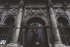 Het jonge meisje bevindt zich op de achtergrond van de oude gotische muur Stock Foto