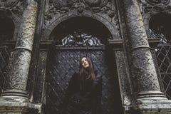 Het jonge meisje bevindt zich op de achtergrond van de oude gotische muur Royalty-vrije Stock Fotografie