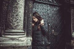 Het jonge meisje bevindt zich op de achtergrond van de oude gotische muur Stock Afbeeldingen