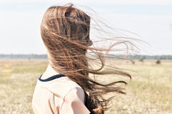 Het jonge meisje bevindt zich op het gebied en de wind fladdert haar haar Stock Foto