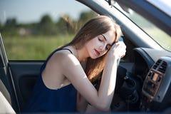 Het jonge meisje bij het wiel van de auto viel in slaap, leggend haar hoofd Royalty-vrije Stock Foto's