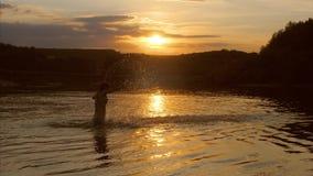 Het jonge meisje bij zonsondergang het spelen in water, meisje overhandigt bespattend water Stock Foto