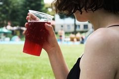 Het jonge meisje in bikini met rode limonade in hand met defocused sw Royalty-vrije Stock Afbeelding