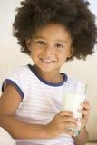 Het jonge meisje binnen het drinken melk glimlachen stock foto