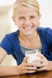 Het jonge meisje binnen het drinken melk glimlachen royalty-vrije stock afbeelding