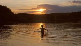 Het jonge meisje danst in water en bekijkt de zonsondergang, Langzame motie Stock Foto