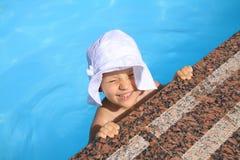 het jonge meisje in de hoed zwemt in het zwembad Royalty-vrije Stock Afbeeldingen