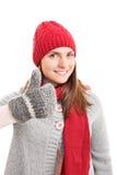 Het jonge meisje in de winterkleren het houden beduimelt omhoog stock afbeelding