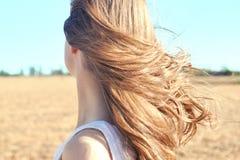 Het jonge meisje in de witte kledingstribunes in het gebied en de wind fladdert haar haar Royalty-vrije Stock Foto's