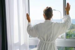 Het jonge meisje dichtbij een venster die het overzees bekijken zonnige ochtend Stock Afbeeldingen