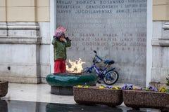 Het jonge meisje die van Rome in de regen voor de eeuwige vlam van een WO.II-monument in het centrum van Sarajevo proberen op te  royalty-vrije stock afbeeldingen
