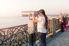 Het jonge meisje die in witte t-shirt door een muntstuk kijken stelde verrekijkers op de overzeese kust in werking De vrouw kijkt Royalty-vrije Stock Afbeelding