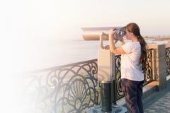 Het jonge meisje die in witte t-shirt door een muntstuk kijken stelde verrekijkers op de overzeese kust in werking De vrouw kijkt Royalty-vrije Stock Afbeeldingen