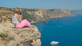 Het jonge meisje doet dichtbij foto aan de blauwe overzeese zitting op een berg stock video
