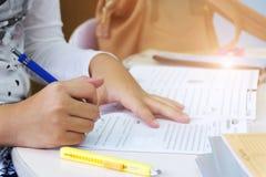 Het jonge meisje doet thuiswerk door potlood stock foto