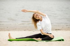Het jonge meisje doet zich het uitrekken op yogamat op zandig strand op een warme dag royalty-vrije stock foto's