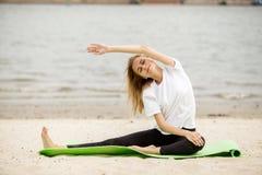 Het jonge meisje doet zich het uitrekken op yogamat op zandig strand op een warme dag royalty-vrije stock foto