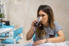 Het jonge meisje drinken op een terras stock fotografie