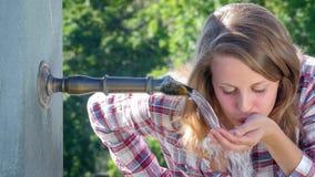 Het jonge meisje drinken van een waterfontein stock footage