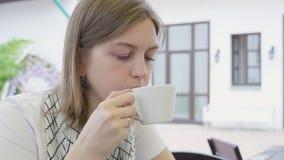 Het jonge meisje drinkt koffie en kijkt stock video