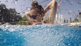 Het jonge meisje duikt in zwembad stock video