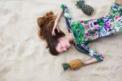 Het jonge meisje in een groene kleding, een lezhitna op zand met ananassen in handen, het modieuze meisje met ananassen Stock Afbeelding