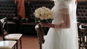 Het jonge meisje in een huwelijkskleding houdt een boeket van de bruid Close-up Het boeket van het huwelijk Mooi bruids boeket bi stock footage