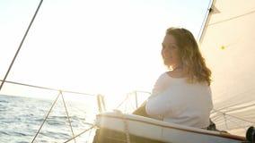 Het jonge meisje in een kleding zit op het dek van een varend jacht dichtbij de mast stock videobeelden