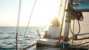 Het jonge meisje in een kleding zit op het dek van een varend jacht dichtbij de mast stock footage