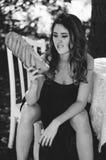 Het jonge meisje in een lange avondjurk zit bij een witte lijst in een park en houdt een brood in haar handen Zwart-witte fotogra Royalty-vrije Stock Afbeelding