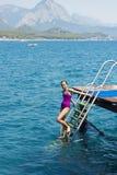 Het jonge meisje in een purper zwempak daalt van een pijler in s stock afbeelding