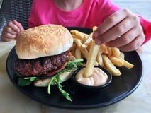 Het jonge meisje eet een grote hamburger met spaanders Royalty-vrije Stock Afbeelding