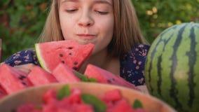 Het jonge meisje eet een heerlijke watermeloenplak - sluit omhoog stock video