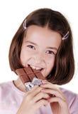 Het jonge meisje eet reep chocolade stock afbeelding