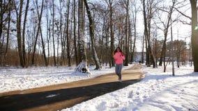 Het jonge meisje gaat binnen voor sporten in de winterpark stock videobeelden