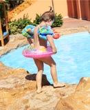 Het jonge meisje gaat in het zwembad Stock Foto's